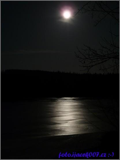 pohled na zamrzlou řeku a nad ní měsíc