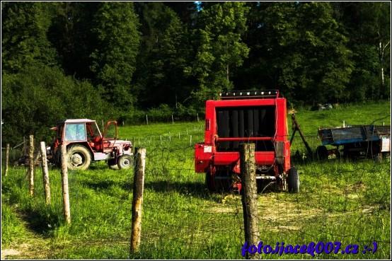 Pohled na louku plnou zemědělských stroju.