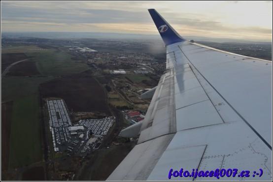 pohled na zem pod křídlem letadla než nabere letadlo tu správnou výšku