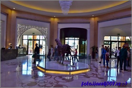 hlavní hala hotelu s sochou koně a recepcí