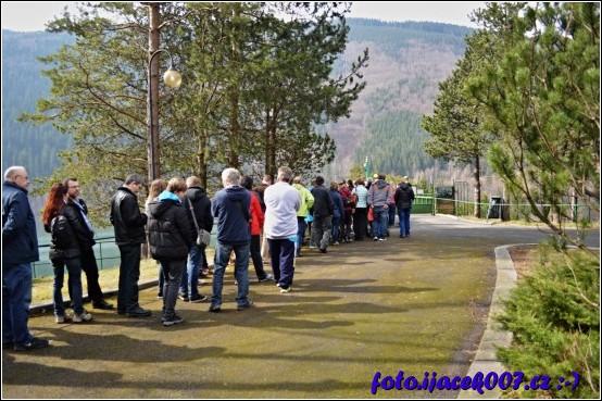 pohled na návštěvníky čekající na vpuštění do areálu u koruny hráze.