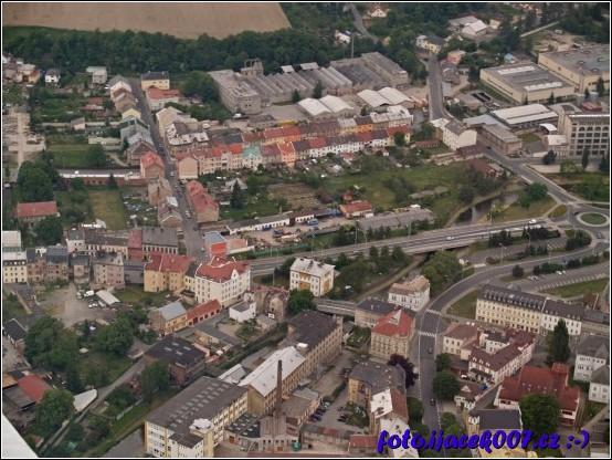 pohled na již neexistující zahradnictvý v Krnově pod ním ulice soukenická v pravé části kruhový objezd.