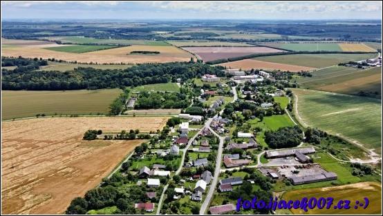 Pohled na celou obec v dálce je vidět zámek.